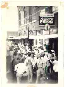 Old, black and white photo of crowd near building with Coca-Cola sign